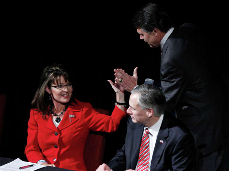 Texas Gov. Rick Perry, right, greets former Alaska Gov. Sarah Palin and Attorney General Greg Abbott after Perry's introduction at an anti-abortion fundraising event in Dallas. AP Photo/LM Otero / AP