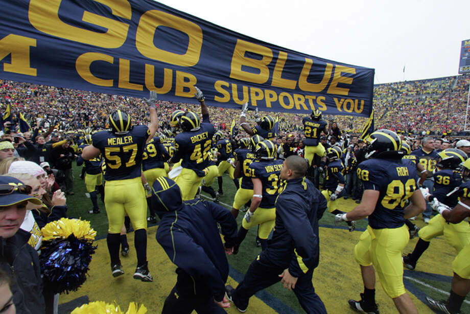 Go Blue, Michigan: The Bump Elliott years were not particularly good ones for the Wolverines, but he is credited with helping start one very cool tradition in 1962 when he allowed the Wolverines to take the field at the Big House running under a huge GO BLUE banner. It measures 40-feet long by 4-feet wide and the players touch it for luck as they pass by. Michigan's defense clearly hasn't been touching the banner enough lately. / FR143848 AP