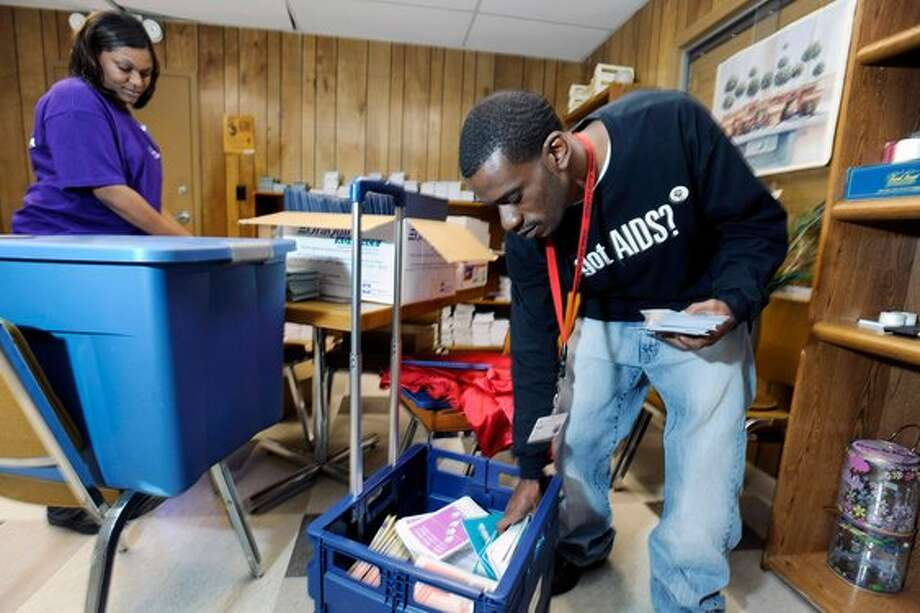 Prevention specialists Andria Williams, left, and Jarrett Jones, with Triangle Aids Network in Beaumont,  prepare educational materials for their 23rd annual AIDS Update Conference on Wednesday.   Valentino Mauricio/The Enterprise / Beaumont