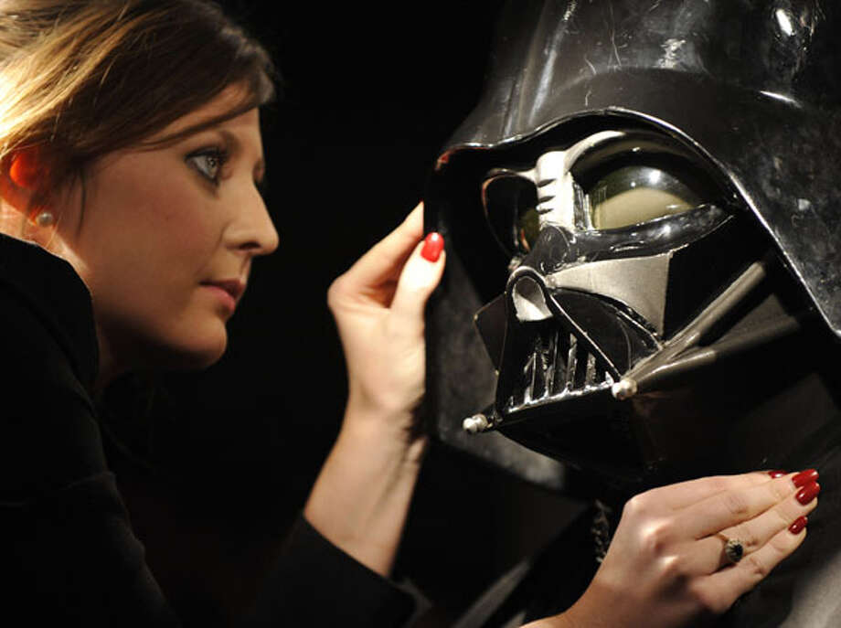 "Christie's employee Caitlin Graham poses with a Darth Vader costume in London. The helmet, mask, shoulder armor and shin guards of the costume were produced for the second Star Wars movie, ""The Empire Strikes Back,"" released in 1980. On Nov. 25, the costume will be offered at Christie's South Kensington and is expected to realise 160,000 GBP to 230,000 GBP. AP Photo/Lennart Preiss / AP"
