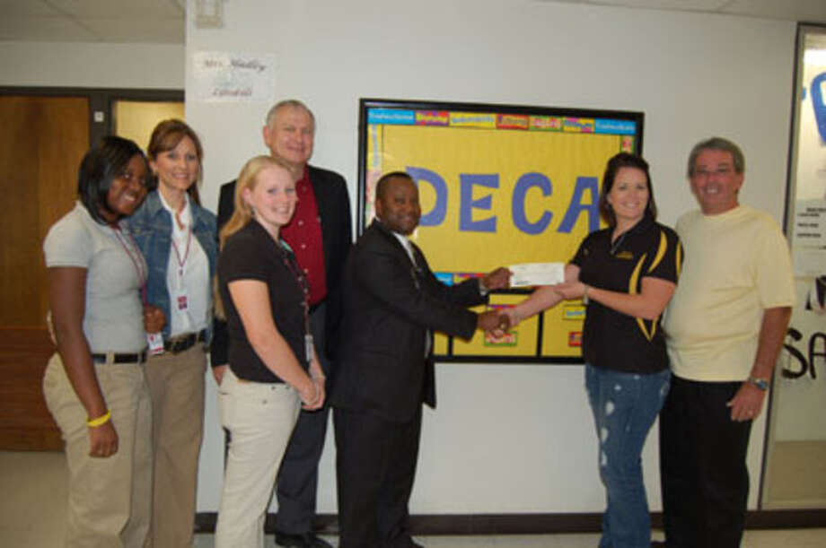 Bob & Nicole Sealy present a $2,000 check to Principal Victor Williams for the DECA program, accompanied by Career Tech Director Dr. Dean Miller, DECA Director Martha Morian and DECA members