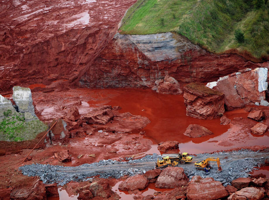 An aerial view of excavators working at a broken dyke of a reservoir that contained red mud of an alumina factory near Ajka, southwest of Budapest, Hungary. The dyke broke on Monday, and more than one million cubic meters of the poisonous chemical sludge inundated three villages, killing a number of people, injuring more than a hundred and causing hundreds of families be evacuated. AP Photo/MTI, Sandor H. Szabo / MTI