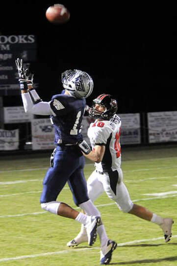 WOS's Mark Roberts catches a pass as Kirbyville's Justin Keene defends at West Orange-Stark High Sch