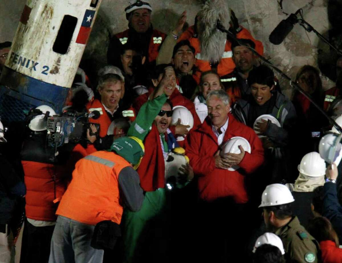 Miner Luis Urzua, the last miner to be rescued, center wearing green, celebrates next to Chile's President Sebastian Pinera after being rescued from the collapsed San Jose gold and copper mine where he had been trapped with 32 other miners for over two months near Copiapo, Chile, Wednesday Oct. 13, 2010. The 69-day underground ordeal reached its end Wednesday night after 33 trapped miners were hauled up in a cage through a narrow hole drilled through 2,000 feet of rock. (AP Photo/Roberto Candia)