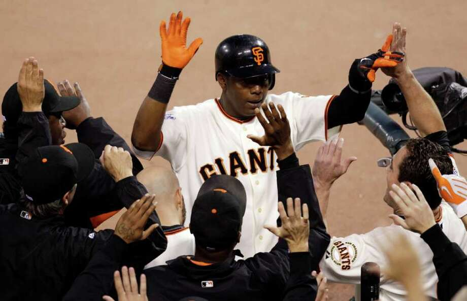 San Francisco Giants' Edgar Renteria is congratulated after hitting a home run during the fifth inning of Game 2 of baseball's World Series against the Texas Rangers Thursday, Oct. 28, 2010, in San Francisco. (AP Photo/Jeff Chiu)