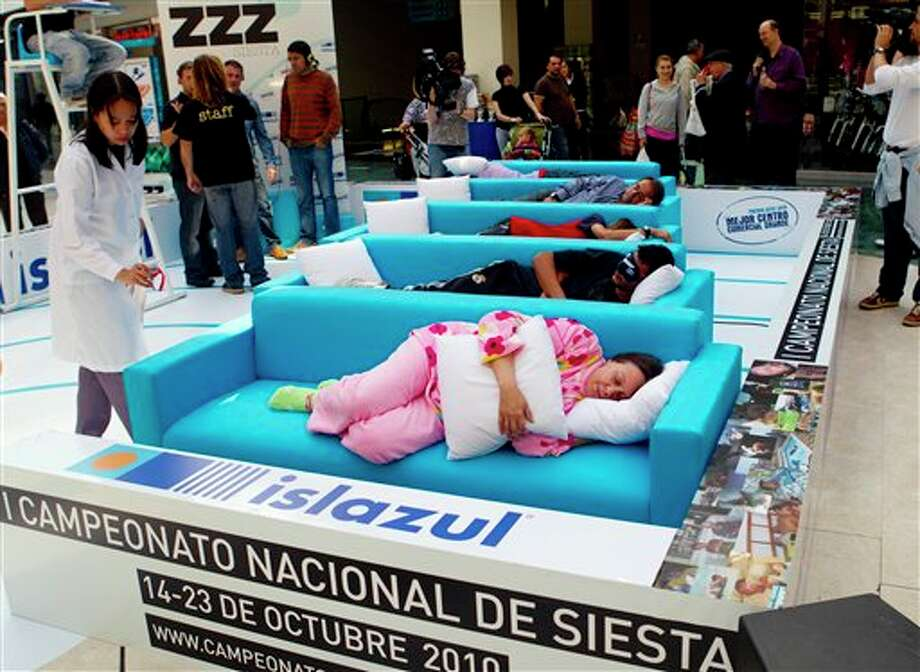 A doctor checks as people sleep a siesta during the first Siesta Championship in Madrid, Thursday, Oct. 14, 2010. The participants of the siesta contest win points for the first person to fall asleep, the loudest snorer, best original sleeping position and best dressed sleeper. Doctors are present to check if the contestants are really asleep. (AP Photo/Paul White) / AP