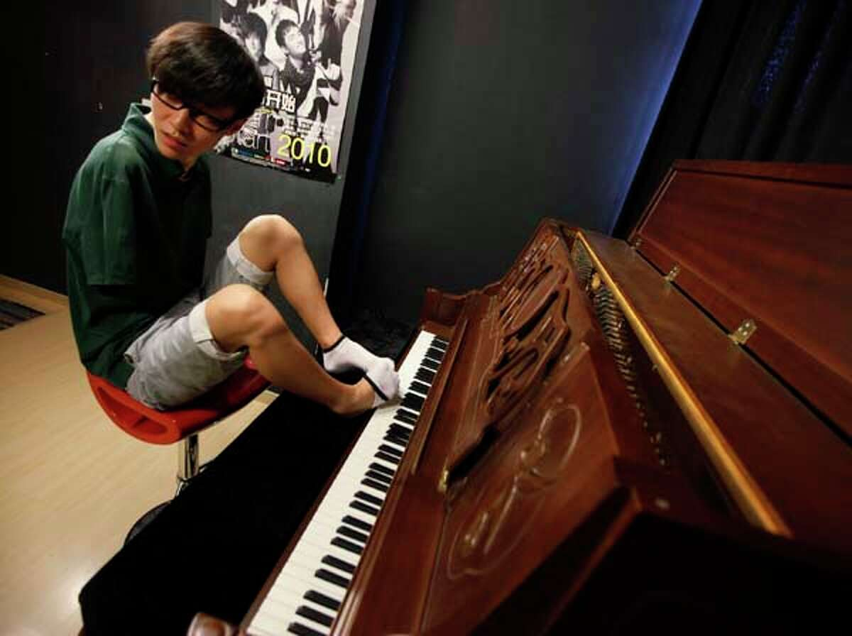 Pianist Liu Wei takes off one of his socks to play a piano before his practice session in Shanghai on Aug. 26. The musician who lost both arms in a childhood accident and plays the piano with his toes won
