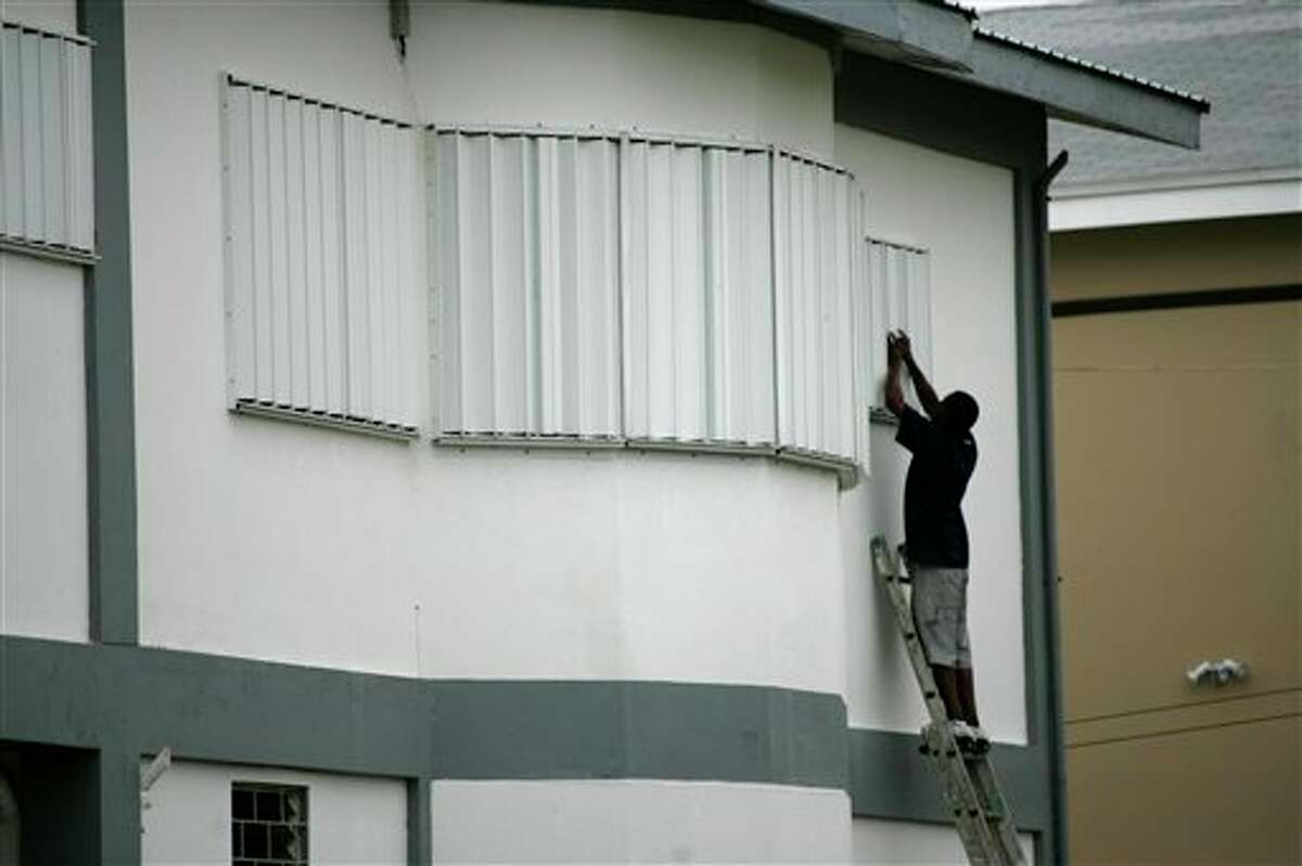 A man sets window protection shutters a few hours before the arrival of Hurricane Richard in Corozal, Belize, Sunday, Oct. 24, 2010. ( AP Photo/Israel Leal)