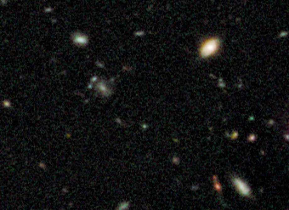 This undated handout image provided by NASA, taken by the Hubble Space Telescope, shows a small smudge, center, that astronomers believe is the oldest thing they have ever seen,light from a long time ago in a galaxy far, far away. (AP Photo/NASA) / NASA