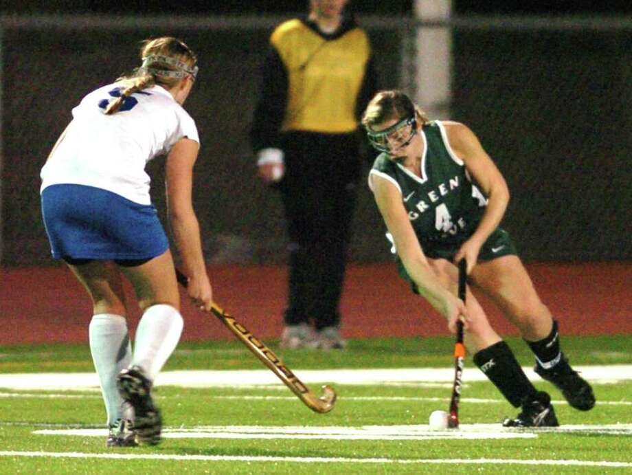 New Milford's 4, Katie Kelly competes with Glastonbury 5, Hayley Hoge during the field hockey game at Watertown High School Nov. 16, 2010. Photo: Chris Ware / The News-Times