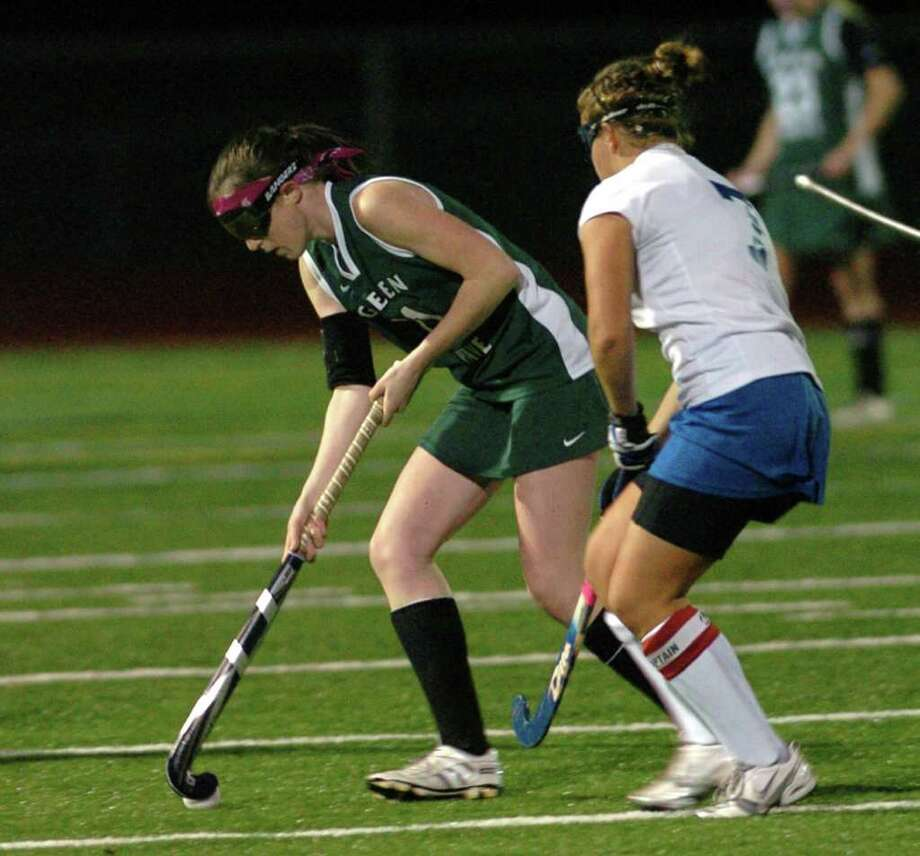 New Milford's 11, Olivia Monteiro competes with Glastonbury's 7, Taylor Moreau during the field hockey game at Watertown High School Nov. 16, 2010. Photo: Chris Ware / The News-Times