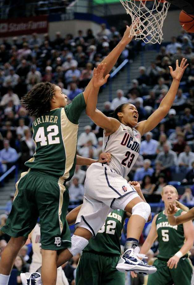 Connecticut's Maya Moore, right, drives to the basket past Baylor's Brittney Griner during the first half of an NCAA college basketball game in Hartford, Conn., on Tuesday, Nov. 16, 2010. (AP Photo/Fred Beckham) Photo: AP