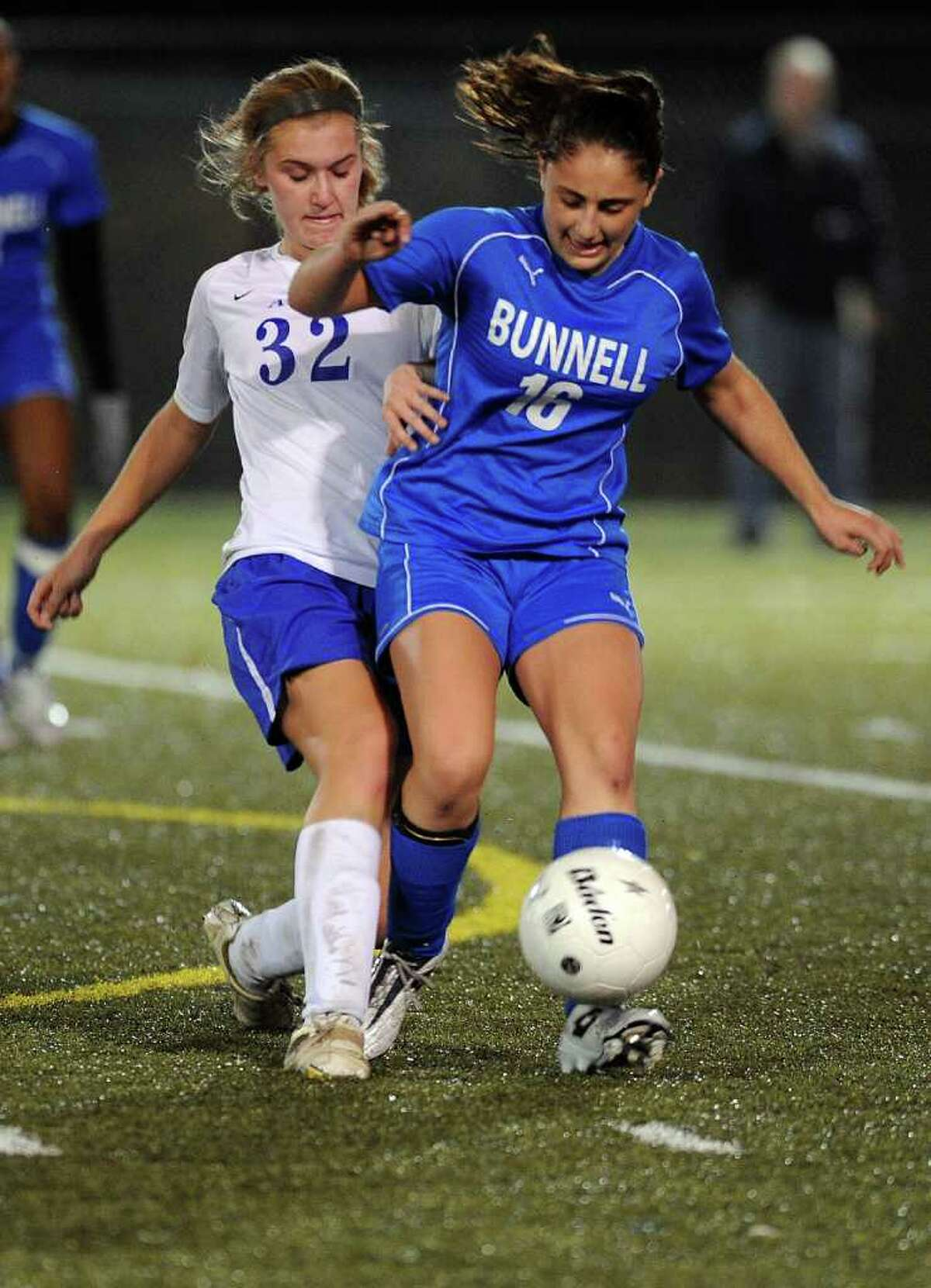 Bunnell's Kacie O'Neill kicks the ball away from an Avon's Sarah Gerali during the State Tournament Class L Semifinal game at Municipal Stadium in Waterbury on Tuesday, November 16, 2010.