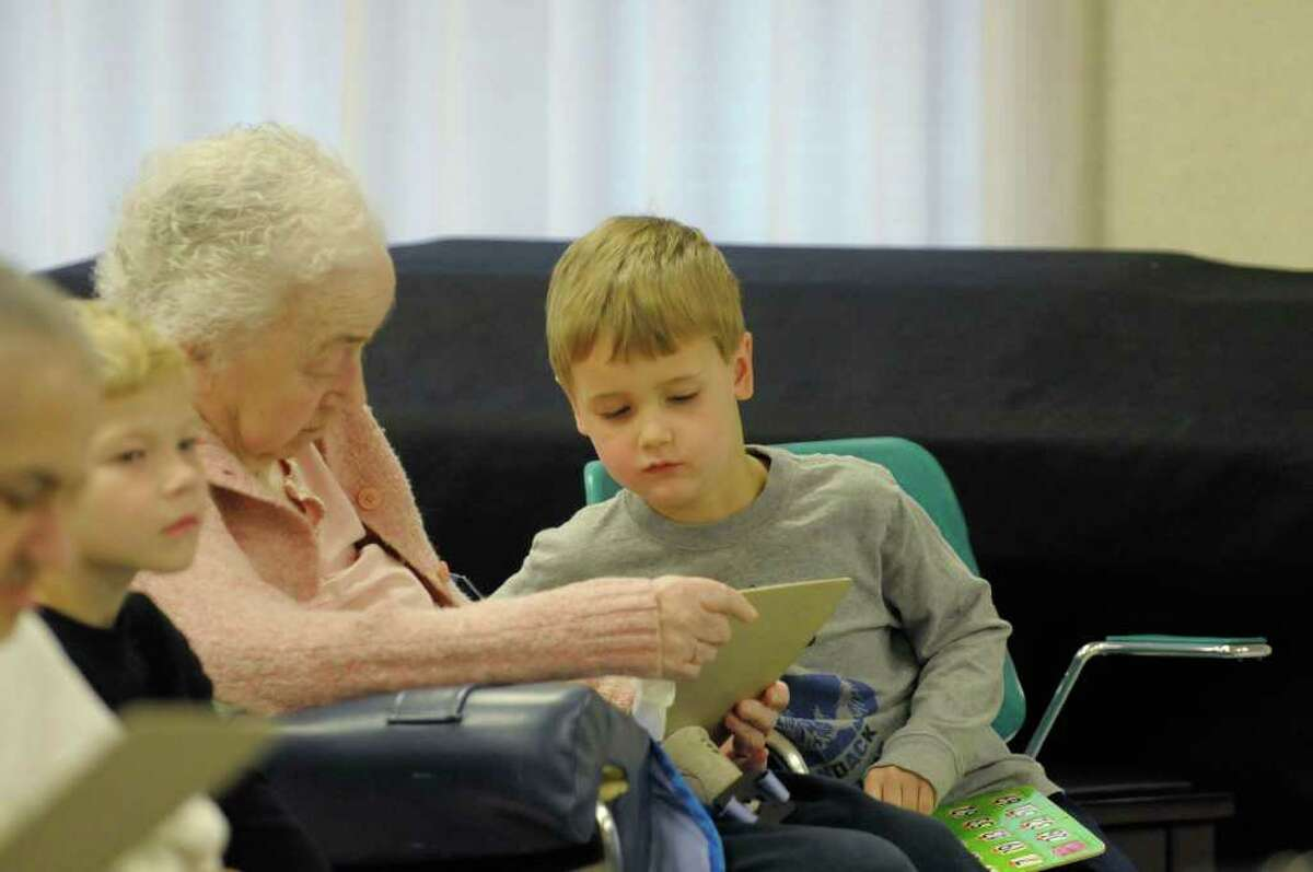 Resident Martha Roy, left, gets help with the bingo card from Miller Hill ? Sand Lake Elementary School student Wyatt Thorsen as residents and students played bingo at the Van Rensselaer Manor Nursing Home in Troy on Tuesday. The Van Rensselaer Manor Nursing Home runs intergenerational programs for its residents two to three times a week. (Paul Buckowski / Times Union)