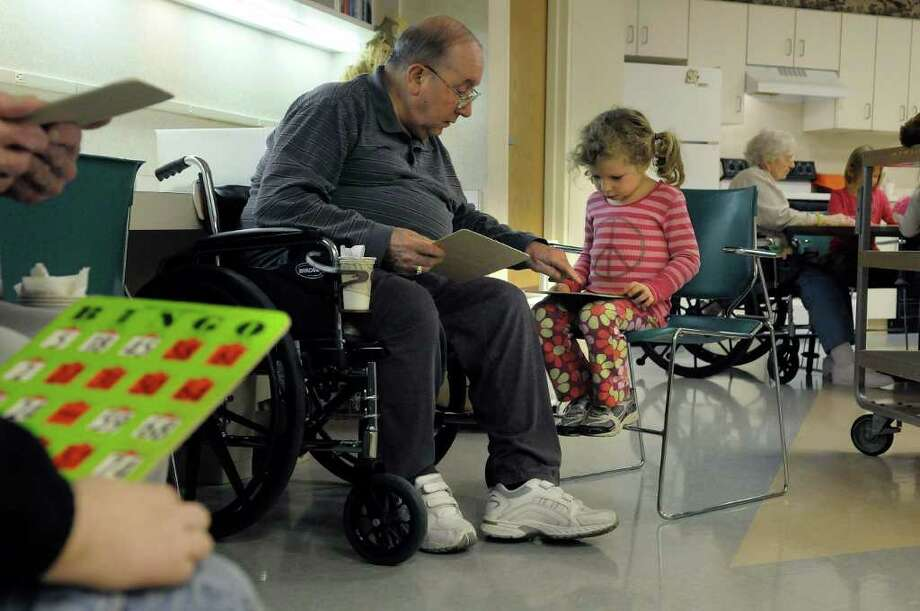 Resident Joe Pasinella, left, helps Miller Hill ? Sand Lake Elementary School student Mia Suscietto with her bingo card as residents and students played bingo  at the Van Rensselaer Manor Nursing Home in Troy on Tuesday. (Paul Buckowski / Times Union) Photo: Paul Buckowski / 00010954A