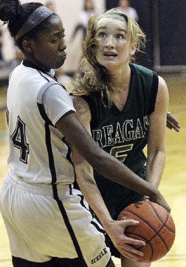 Steele's McKenzie Calvert (left) secures possession of a loose ball against Reagan's Marissa Rodriguez on Tuesday night.