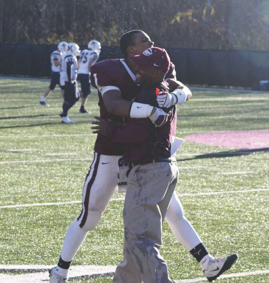 St. Luke's sophomore Blake Stroman leaps into the arms of an assistant coach after Saturday's 48-20 win. Photo: Matt Norlander / New Canaan News