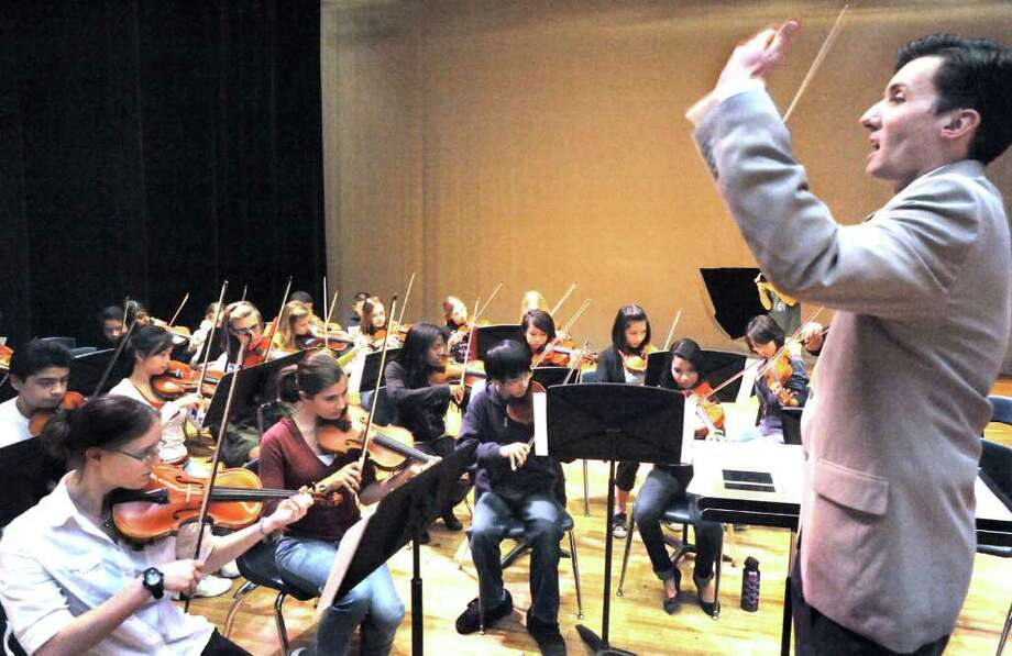 Todd Sullivan, conductor of the Boston String Quartet, right, leads the Danbury High School orchestra during a rehearsal, Wednesday, Nov. 17, 2010. A combined performance of the quartet and students will take place at the high school on Thursday night as part of the Boston String Quartet's Xibus tour. Photo: Michael Duffy / The News-Times