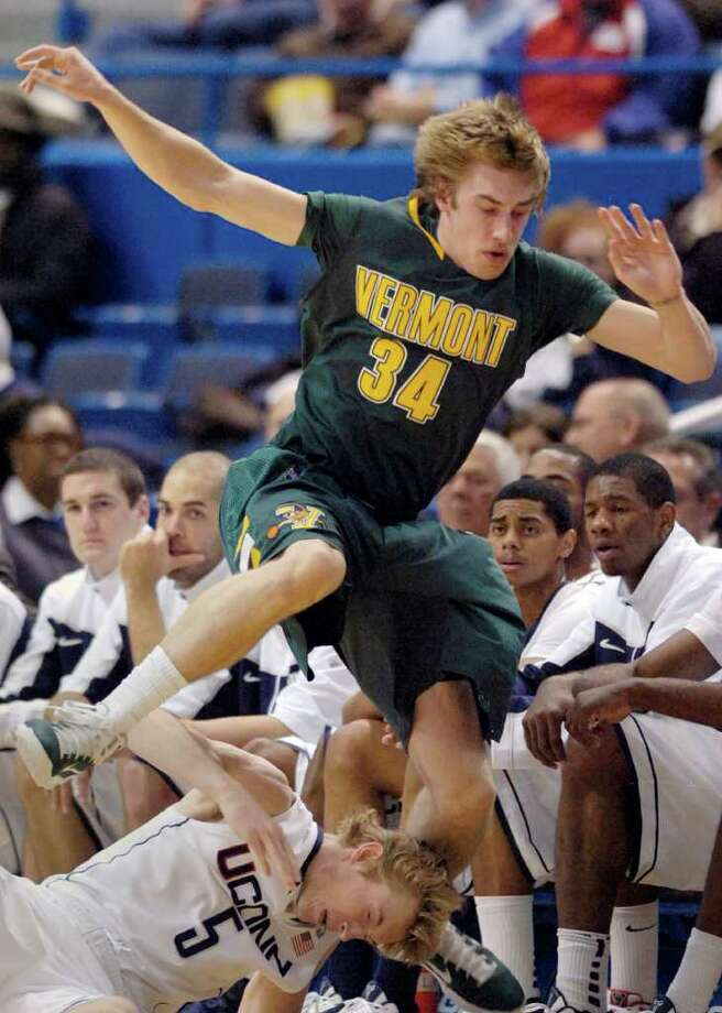 Connecticut's Niels Giffey, bottom, gets tangled with Vermont's Matt Glass during the first half of an NCAA college basketball game in Hartford, Conn., on Wednesday, Nov. 17, 2010. (AP Photo/Fred Beckham) Photo: AP