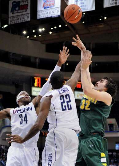 Vermont's Evan Fjeld, right, shoots over Connecticut's Roscoe Smith, center, and Alex Oriakhi during