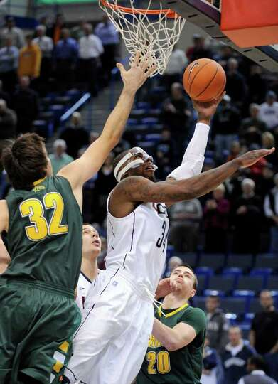 Connecticut's Alex Oriakhi, right, drives past Vermont's Evan Fjeld during the first half of an NCAA