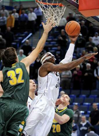 Connecticut's Alex Oriakhi, right, drives past Vermont's Evan Fjeld during the first half of an NCAA college basketball game in Hartford, Conn., on Wednesday, Nov. 17, 2010. (AP Photo/Fred Beckham) Photo: AP