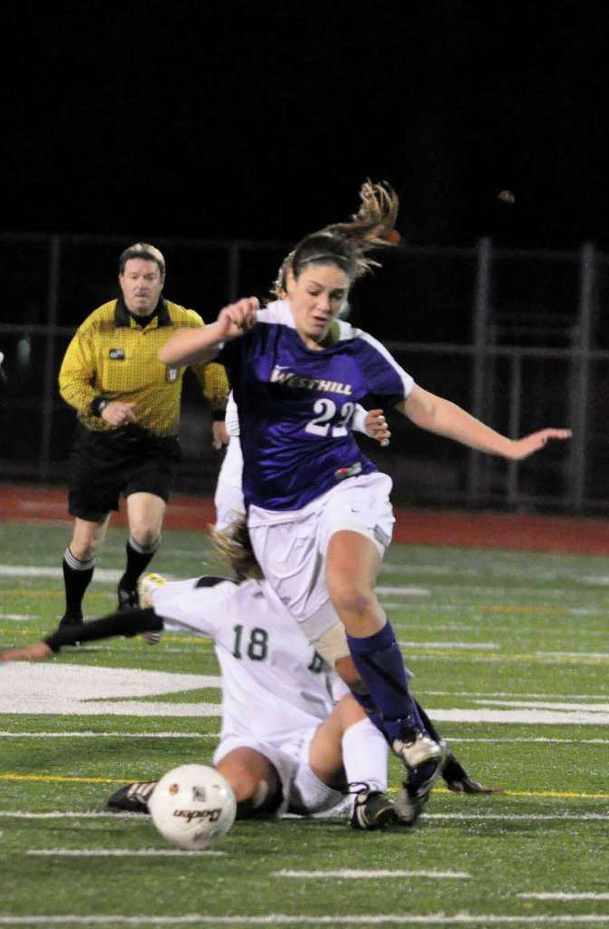 Westhill's Teressa Dunster gets tripped up by Hamden's Gabby Benitez during the Class LL girls soccer semifinals at Norwalk High on Wednesday, Nov. 17, 2010.
