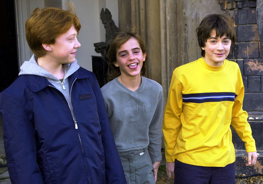 "Rupert Grint, who plays Ron Weasley in the ""Harry Potter"" films, Emma Watson, who plays Hermione Granger, and Daniel Radcliffe, who plays Harry Potter, chat at a news conference before the premiere of ""Harry Potter and the Philosopher's Stone"" in 2001. Adam Butler/The Associated Press"