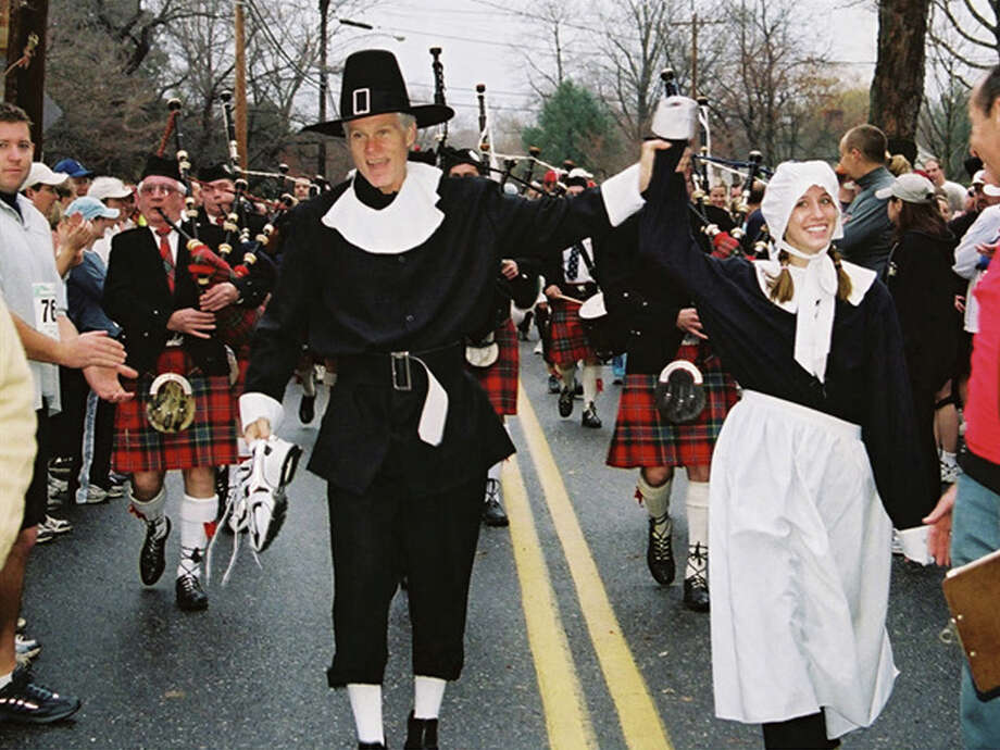 Pequot club members, Ray Rodgers and Anna Griffin, dressed in pilgrim garb leading the annual procession of bagpipers and runners to the starting line of the annual Thanksgiving Day road race and walk sponsored by the Pequot Runners. Photo: Contributed Photo / Connecticut Post Contributed