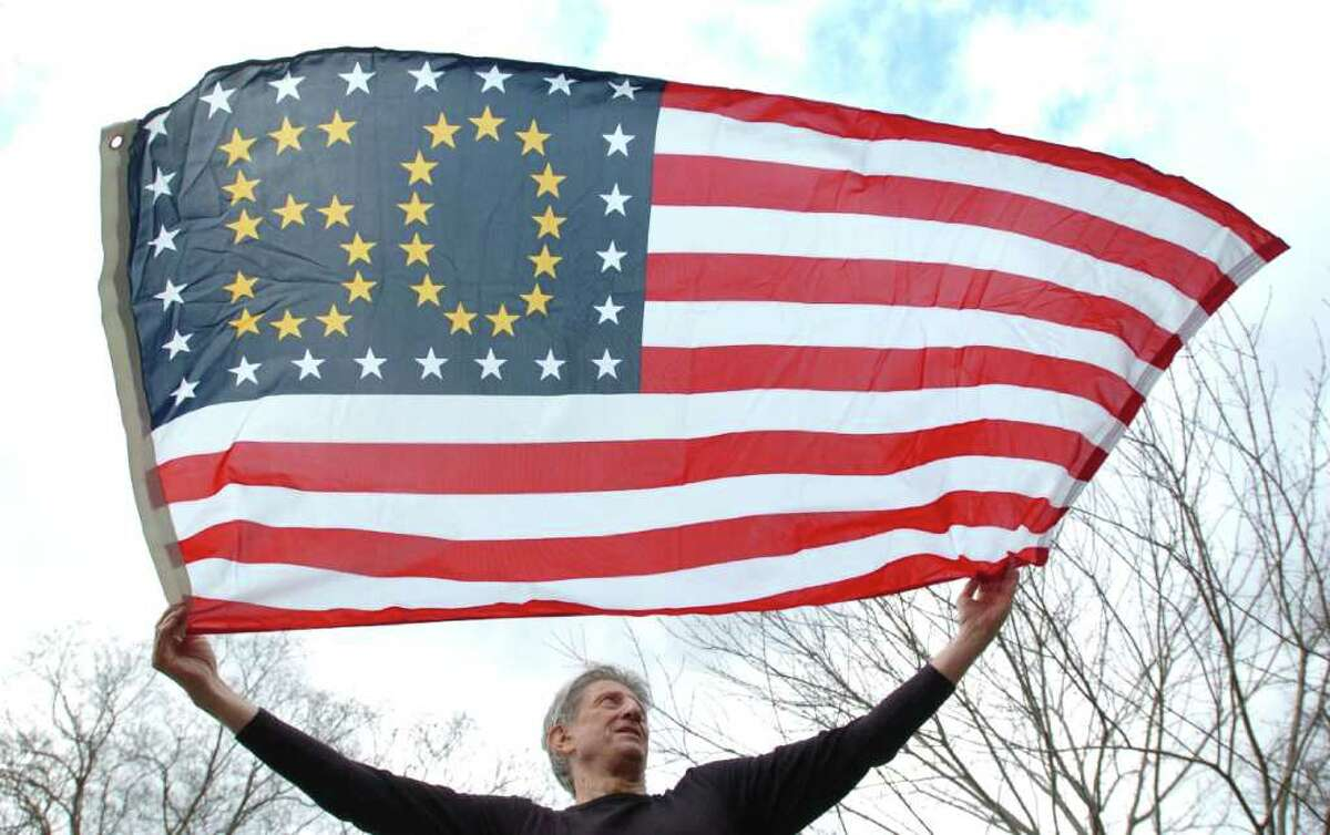 """Peter Orenski, of New Milford, holds an American flag he designed to honor the Golden Jubilee of the American flag. The jubilee celebrates the 50th anniversary of the design, which has been flying since July 4, 1960. """"I'm a kid from Romania gifting a special flag to his adopted country,"""" said Orenski."""