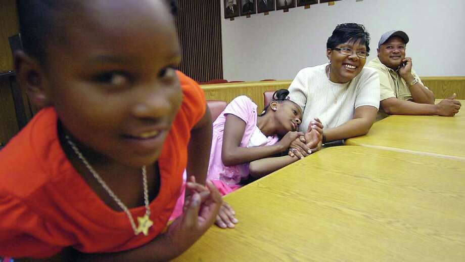 Aneva and Ronald Edwards, right, will be new parents Friday when they get through the Jefferson County National Adoption Day ceremony being held at the courthouse. The Edwards, will be officially adopting Shanell, left, and Aqueliah, right,  two out of the twenty kids that will be adopted into 12 forever homes in the ceremony.  Dave Ryan/The Enterprise Photo: Dave Ryan / Beaumont