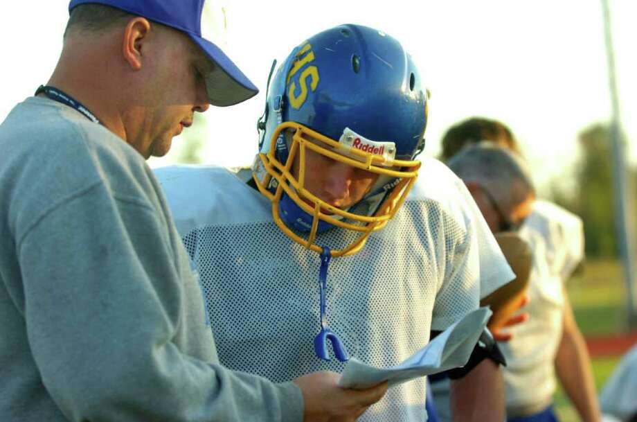 Evadale head football coach Mark Williams, left, goes over a play with quarterback Billy Nichols during practice on Wednesday, November 17, 2010.  Valentino Mauricio/The Enterprise Photo: Valentino Mauricio / Beaumont