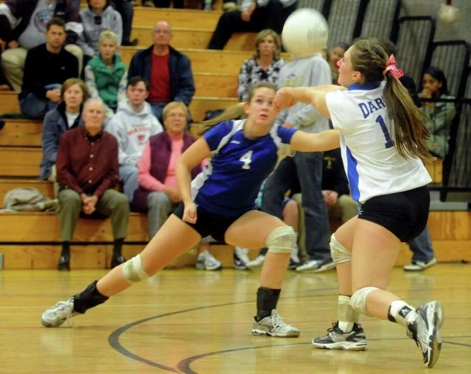 Darien's Bella Carrara, right, and Mackenzie Begley, left, both reach for the ball during the Girls Volleyball State Tournament Class L Semifinal game against Farmington at Woodland High School on Thursday, November 18, 2010. Photo: Lindsay Niegelberg / Connecticut Post