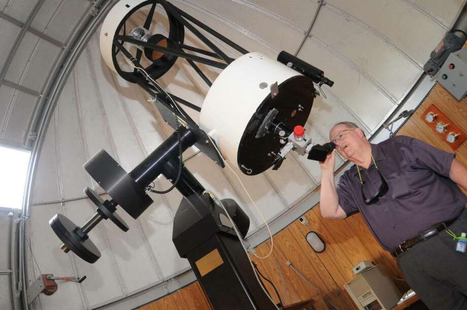Western Connecticut State Universities astronomy Professor, Dr. Dennis Dawson, looks through the lens of the Ritchey-Chretien telescope that is located at the observatory on the west side campus on Thursday Sept. 10, 2009 Photo: Lisa Weir / The News-Times