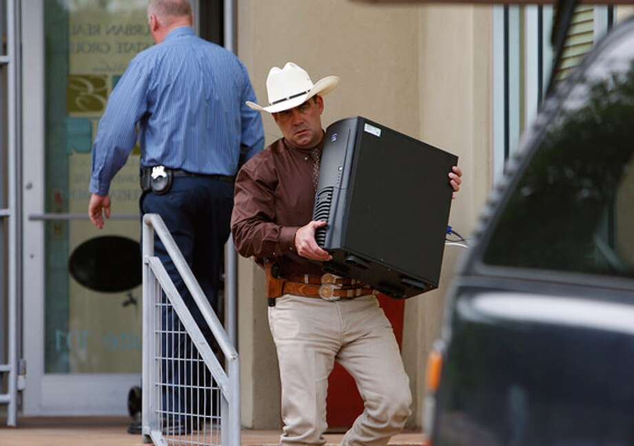 Officials with the Texas Rangers and the district attorney's office search Gary Cain's office in April, seizing documents, records and computer files.