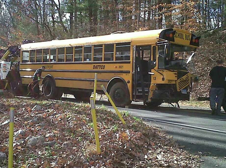 A wrecking crew prepares to haul away a Westport school bus that was involved in an accident at approximately 8:30 a.m. on Friday, Nov. 19, 2010, near the intersection of Lyons Plains Road and North Avenue. The driver was transported to Norwalk Hospital for an apparent broken leg and one of the 23 elementary students on board suffered minor injuries and was turned over to the custody of parents, according to Weston police. Photo: Stephanie Paulino, Gary Jeanfaivre / Westport News