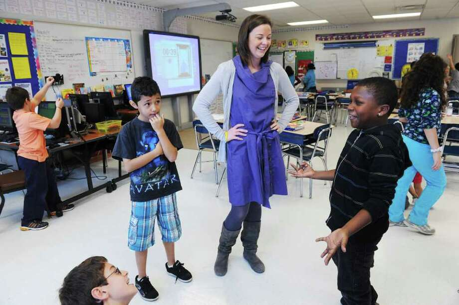 Advocate reporter Maggie Gordon with fourth-graders Enart Dibra, David Torres and Kiefer Frager-Akings in Room 256 during math class at Stark Elementary School in Stamford, Conn. on Wednesday November 17, 2010 Photo: Kathleen O'Rourke / Stamford Advocate