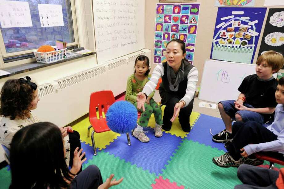 Mandarin Chinese language teacher Jing Tan uses a ball as an educational tool for her students during a class of the Chinese Language School of Connecticut at the Second Congregational Church, Greenwich, Thursday afternoon, Nov. 18, 2010.  When a student catches the ball they must say a wordor phrase in Mandarin. Photo: Bob Luckey / Greenwich Time