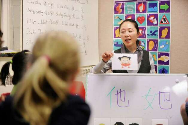 Mandarin Chinese language teacher Jing Tan uses pictures as an educational tool for the names of family members during a class of the Chinese Language School of Connecticut at the Second Congregational Church, Greenwich, Thursday afternoon, Nov. 18, 2010. Photo: Bob Luckey / Greenwich Time
