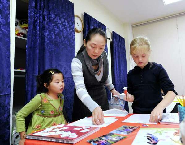 Mandarin Chinese language teacher Jing Tan, center, does an exercise using Chinese characters with students, Shelley Kane, 6, left, and Ellie Jaffe, 7, right, during a class of the Chinese Language School of Connecticut at the Second Congregational Church, Greenwich, Thursday afternoon, Nov. 18, 2010. Photo: Bob Luckey / Greenwich Time