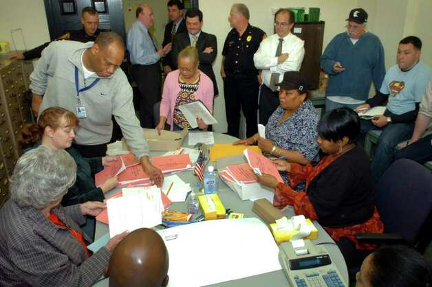 Republican registrar of voters Joseph Borges (standing left) and Santa Ayala, the Democratic registrar of voters in Bridgeport (standing center) begin the process of verifying the moderator reports from each of the the city's 25 voting precincts Thursday afternoon, Nov. 4th, 2010. Photo: Ned Gerard / Connecticut Post