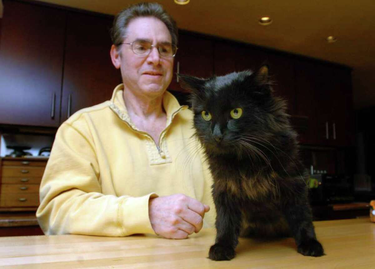 Jerrold Siegel and his cat Zeus are shown together at their Sherman home Thursday Nov. 19, 2010, enjoying each others company after Zeus had been missing for 15 days.