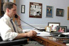 U.S. Rep. Jim Himes, D-Conn., in his Washington, D.C., office this past summer. Family photos, from left, a wedding photo, photos of his two daughters and a photo of Himes and his wife Mary, are shown on his desk.