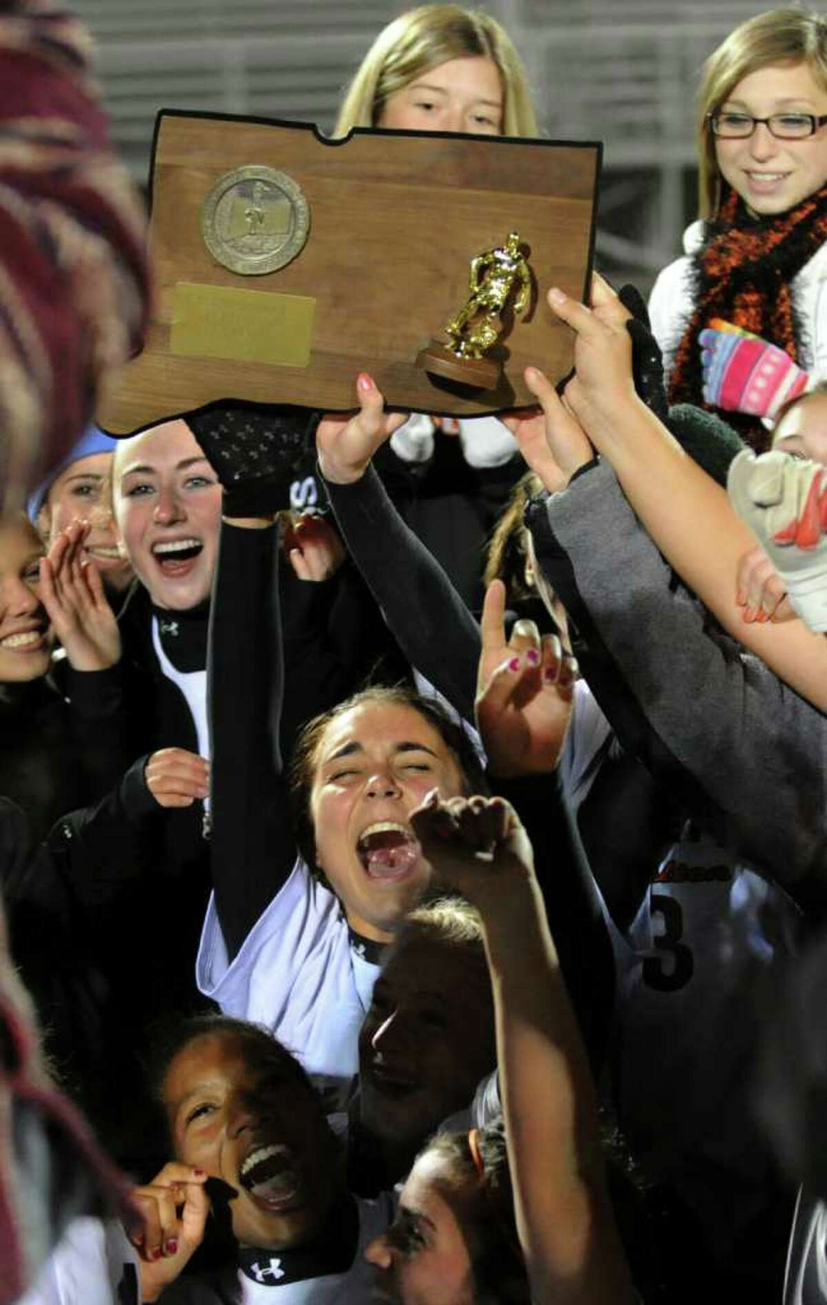 Shelton team members cheer as they hold up the trophy after beating Westhill in Class LL girls final championship soccer in Norwalk, Conn. on Friday November 19, 2010.
