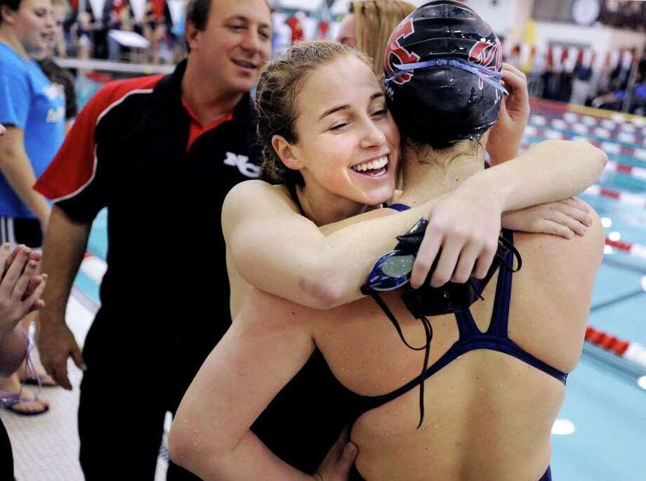 Swimmer Allie Skaperdas, left,  of New Canaan High School, hugs teammate Jenna Egan the FCIAC Swimming Championships at Greenwich High School, Saturday, Nov. 6, 2010. Photo: Bob Luckey, ST / Greenwich Time