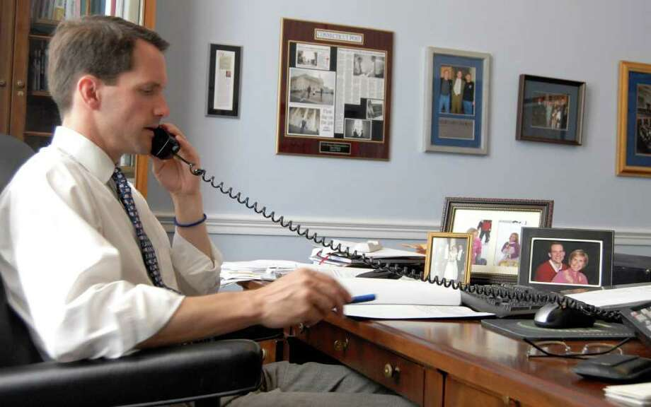 U.S. Rep. Jim Himes, D-Conn., in his Washington, D.C., office this past summer. Family photos, from left, a wedding photo, photos of his two daughters and a photo of Himes and his wife Mary, are shown on his desk. Photo: File Photo / Greenwich Time File Photo