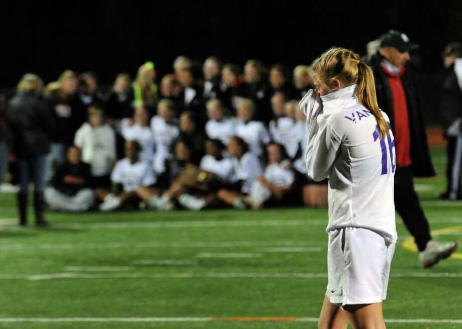 As Shelton gets its team photo taken with the trophy, Westhill's #16 Elizabeth Van name walks back to the bench dejected, after the team lost to Shelton in Class LL girls final championship soccer in Norwalk, Conn. on Friday November 19, 2010. Photo: Christian Abraham / Connecticut Post