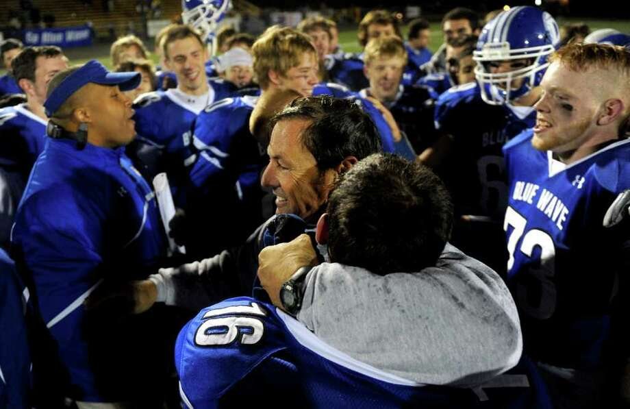 The Darien football team, including coach Rob Trifone, center, celebrate winning Friday's FCIAC football championship game at Trumbull High School on November 19, 2010. Photo: Lindsay Niegelberg / Connecticut Post