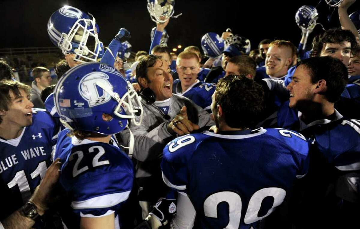 The Darien football team, including coach Rob Trifone, center, celebrate winning Friday's FCIAC football championship game at Trumbull High School on November 19, 2010.