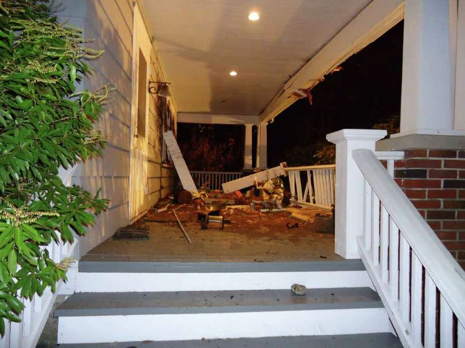 The driver of a Porsche Carrera was trapped for 40 minutes after going airborne for 35 feet and crashing into a house at 24 Highland Ave. in Rowayton late Friday night. Photo: Contributed Photo / Stamford Advocate Contributed